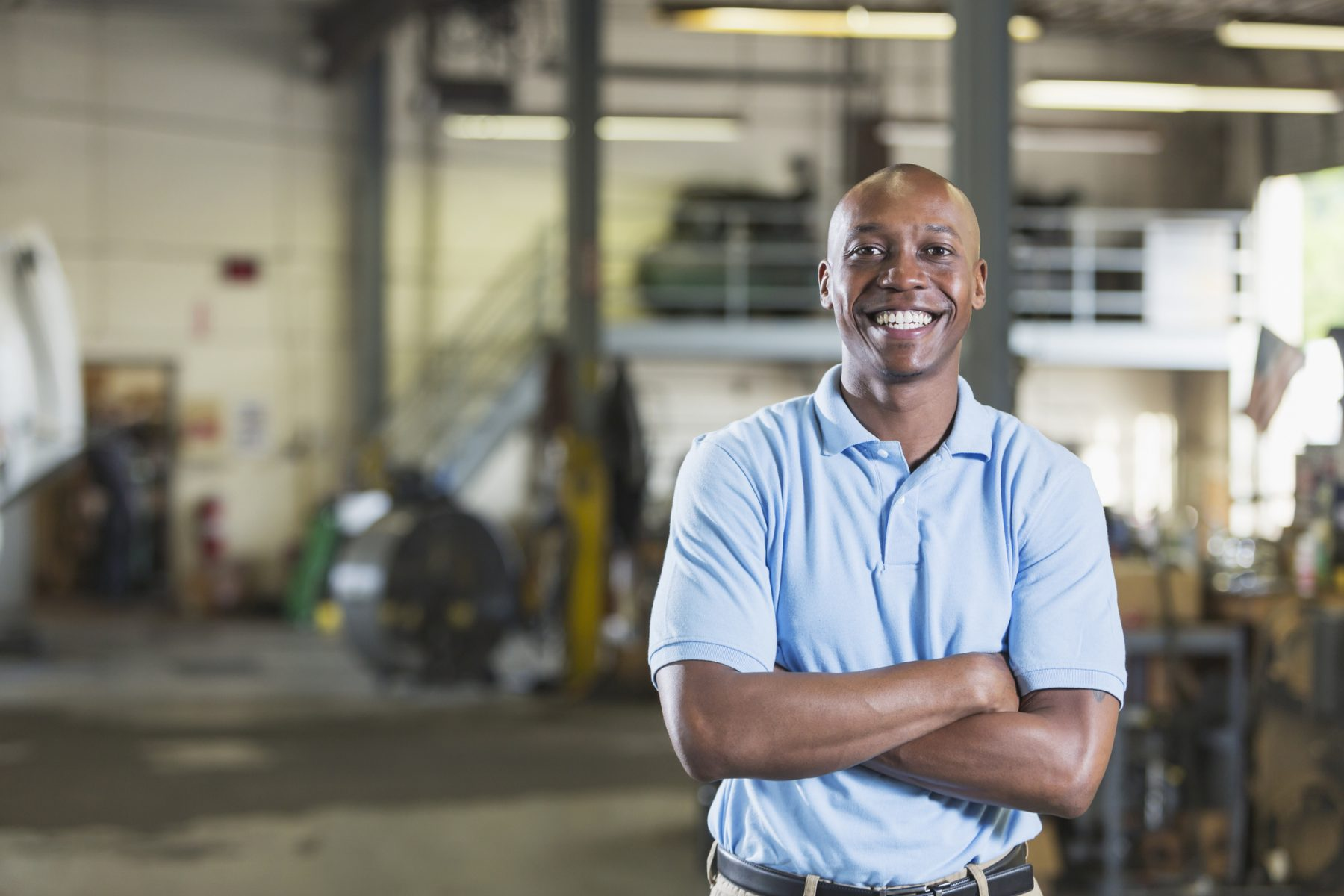An African-American man standing with his arms crossed, smiling at the camera, in a vehicle repair shop.