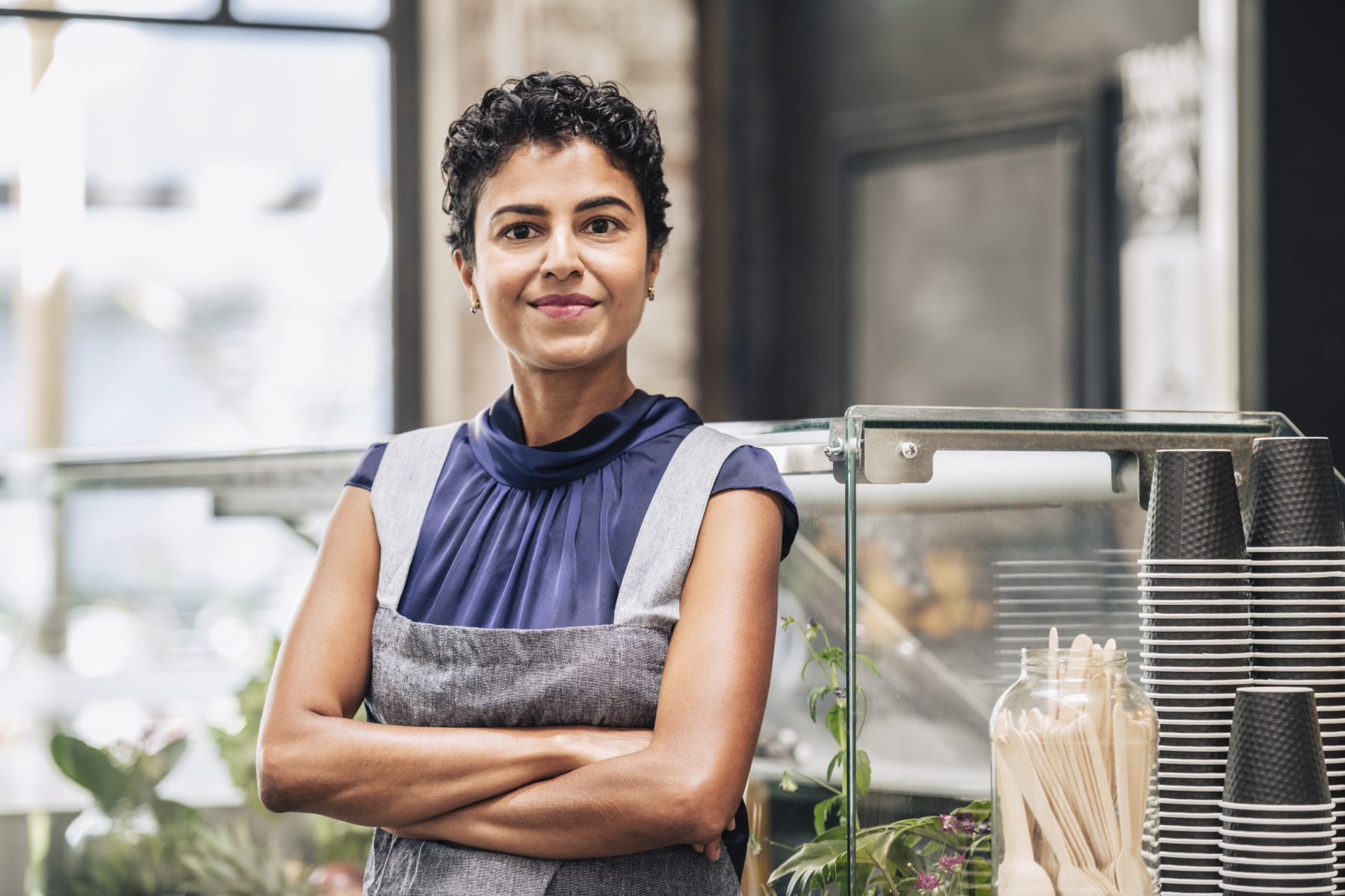 Confident mature woman at work wearing apron at coffee shop.